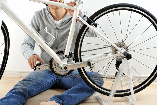 ロードバイクをメンテナンスする男性